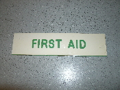 "First Aid Engraved Sign. P/N: 834. 2"" X 8"". Mounts Easily with Double Faced Tape. White with green lettering. UPC: 010736008348. U.S. Stamp Brand."
