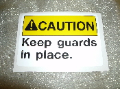 "CAUTION Keep Guards in Place Sign. New. Vinyl Sticker. 3 1/2"" H X 5"" W. Yellow and White with Black Letters."