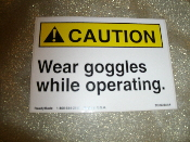 "CAUTION Wear Goggles While Operating Sign. New. Vinyl Laminated Sticker. 3 1/2"" H X 5"" W."