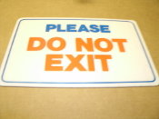"Please Do Not Exit Plastic Sign. Self Stick. New. White background, Blue and Red Lettering. 7 1/2"" H X 11 1/2"" W. Rounded Edges."